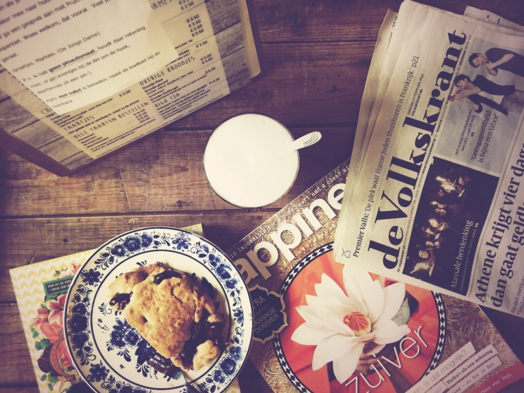 Een houten koffietafel met daarop een cappuccino, een kersengebakje, de Volkskrant, een menukaart van De Jonge Dame in Ede en het tijdschrift Happiness