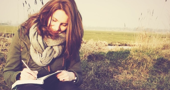 Een close-up van de oprichter van Het SchrijfCafé, Robyn Samsom, die aan het schrijven is.